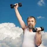 Hombre que ejercita con pesas de gimnasia Imagen de archivo libre de regalías