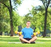 Hombre que ejercita con pesas de gimnasia en parque Fotografía de archivo libre de regalías