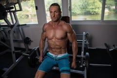Hombre que ejercita el trapecio en el gimnasio Fotografía de archivo libre de regalías