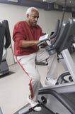 Hombre que ejercita en la bici inmóvil en club de salud Imágenes de archivo libres de regalías