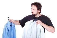 Hombre que elige entre dos camisas fotos de archivo