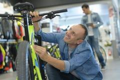 Hombre que elige la bici en la tienda de la bici Foto de archivo libre de regalías
