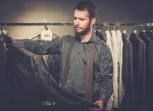 Hombre que elige la chaqueta en la tienda Fotos de archivo libres de regalías