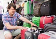 Hombre que elige la maleta en la tienda Foto de archivo