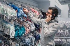 Hombre que elige la ropa interior de la ropa interior para su esposa en tienda del supermercado imagenes de archivo