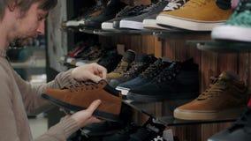Hombre que elige las nuevas zapatillas de deporte en tienda extrema de los deportes, zapatos del monopatín almacen de video