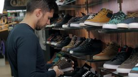 Hombre que elige las nuevas zapatillas de deporte en tienda extrema de los deportes, zapatos del monopatín metrajes