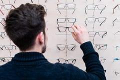 Hombre que elige los vidrios de estante en tienda del óptico Foto de archivo libre de regalías
