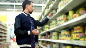 Hombre que elige verduras conservadas en el supermercado almacen de metraje de vídeo
