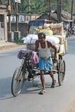 Hombre que empuja el carrito de ciclo pesadamente cargado Fotos de archivo libres de regalías