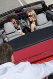 Hombre que empuja el coche conducido por las mujeres Foto de archivo libre de regalías
