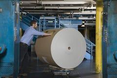 Hombre que empuja el rollo enorme del papel en fábrica Fotografía de archivo