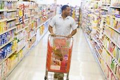 Hombre que empuja la carretilla a lo largo del pasillo del supermercado Fotos de archivo libres de regalías