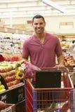 Hombre que empuja la carretilla por el contador de la fruta en supermercado Fotos de archivo libres de regalías