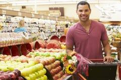 Hombre que empuja la carretilla por el contador de la fruta en supermercado Imagen de archivo