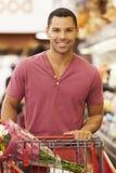 Hombre que empuja la carretilla por el contador de la producción en supermercado Imágenes de archivo libres de regalías