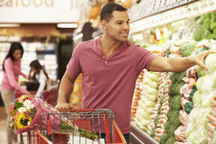 Hombre que empuja la carretilla por el contador de la producción en supermercado Imagenes de archivo