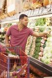 Hombre que empuja la carretilla por el contador de la producción en supermercado Fotos de archivo