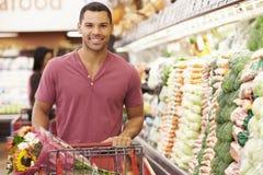Hombre que empuja la carretilla por el contador de la producción en supermercado Fotografía de archivo libre de regalías