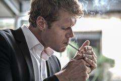 Hombre que enciende un cigarrillo Imagen de archivo libre de regalías