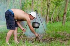Hombre que enciende un fuego de cocinar mientras que acampa Foto de archivo libre de regalías