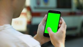 Hombre que enrolla la pantalla táctil del teléfono, concepto de seguimiento de la ambulancia en línea, navegación almacen de metraje de vídeo