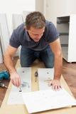 Hombre que ensambla los muebles del paquete plano fotos de archivo