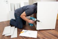 Hombre que ensambla los muebles del paquete plano Imagen de archivo libre de regalías