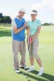 Hombre que entrena a su socio en el putting green Foto de archivo