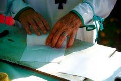 Hombre que envuelve la vela de la cera en el papel en el mercado Foto de archivo libre de regalías
