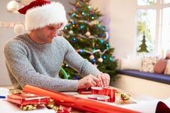 Hombre que envuelve los regalos de la Navidad en casa Fotografía de archivo libre de regalías