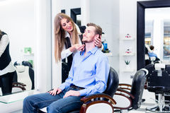 Hombre que es afeitado por la mujer del peluquero Fotografía de archivo