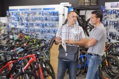 Hombre que es ayudado por el vendedor de la tienda de la bici del deporte Imagen de archivo