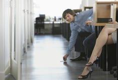 Hombre que escoge las piernas de Pen Off Floor By Woman Imagenes de archivo