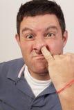 Hombre que escoge su nariz Foto de archivo libre de regalías