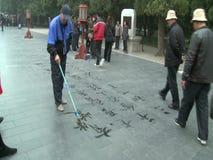 Hombre que escribe caracteres chinos en la acera almacen de metraje de vídeo