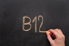 Hombre que escribe la palabra B12 en la pizarra fotos de archivo libres de regalías