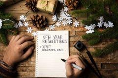 Hombre que escribe la resolución del Año Nuevo en el papel imagen de archivo