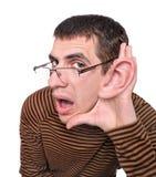 Hombre que escucha con el oído grande. Foto de archivo libre de regalías
