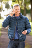 Hombre que escucha el MP3 mientras que recorre en parque Foto de archivo libre de regalías