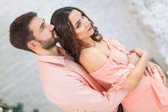 Hombre que escucha el vientre de embarazada feliz Foto de archivo