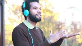Hombre que escucha la música con los auriculares almacen de video