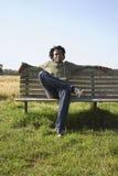 Hombre que escucha la música en banco de parque Imagenes de archivo