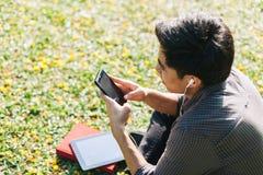 Hombre que escucha la música en su dispositivo Fotografía de archivo libre de regalías