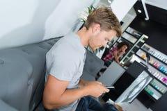 Hombre que espera en el sofá en el salón de la peluquería imagen de archivo