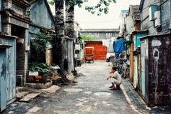 Hombre que espera fuera de su hogar en un hutong típico de la ciudad imagen de archivo libre de regalías