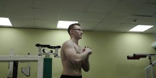 Hombre que estira el brazo antes de entrenamiento del gimnasio Atleta de sexo masculino fuerte de la aptitud que coloca el calent metrajes