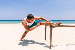 Hombre que estira en la playa Fotografía de archivo libre de regalías