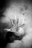 Hombre que estira la mano a través de humo Imágenes de archivo libres de regalías