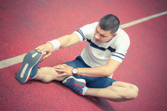Hombre que estira la pierna en la pista corriente Imagenes de archivo